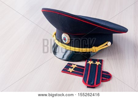 Still cap and insignia of police lieutenant colonel on the table