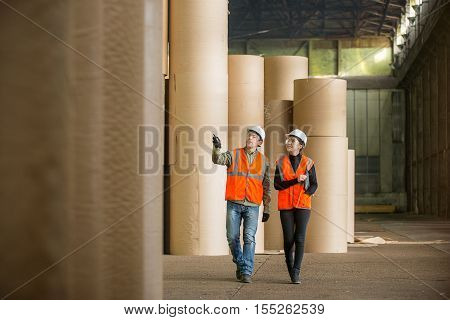 Paper mill factory workers with giant paper rolls on the background
