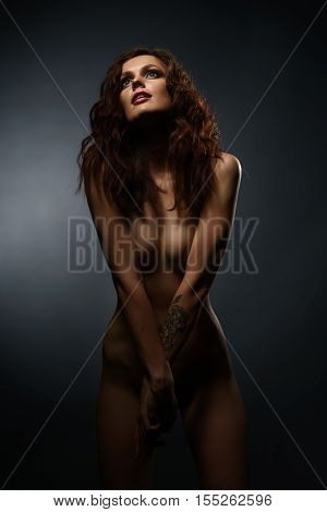 Nude. Vertical photo of skinny brunette with thin waist