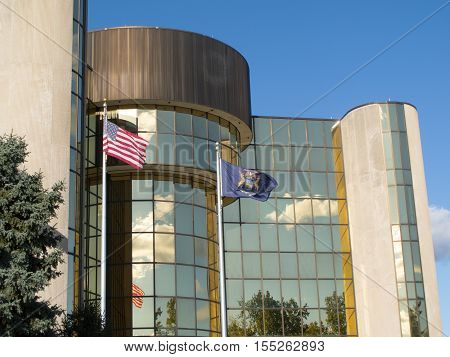Flags of the United States of America and the State of Michigan fly atop flapoles at Livonia City Hall where some of the surrounding landscaping can be seen reflected in its colorful windows.