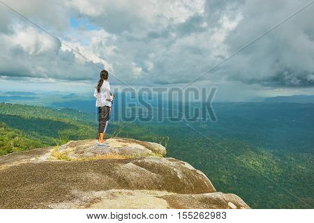 Young woman stands at the cliff over the forest. Traveler is seeing rain cloud over tropical rain-forest.