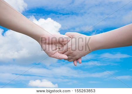 Two hands - woman and man touch each other on sky background