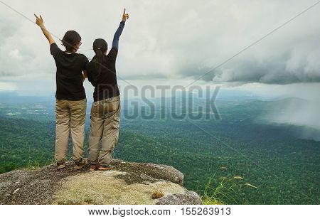 Two friends stand together at the cliff,  raise their arms and see the storm which is coming over tropical rain-forest.