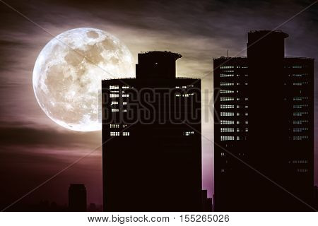 Silhouettes Of Two Skyscrapers Construction With Background Of A Large Moon At Nighttime.