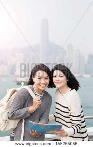 two beauty woman take map and smile to you in hongkong