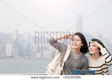 two beauty woman take map and look somewhere in hongkong