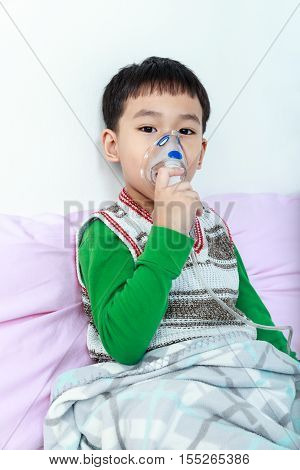 Asian child holds a mask vapor inhaler for treatment of asthma on sickbed in hospital. Breathing through a steam nebulizer. Concept of inhalation therapy apparatus.