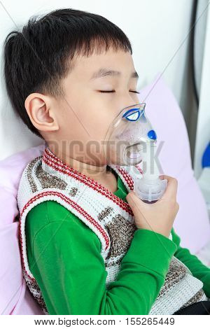 Closeup Asian Child Closing Eyes And Holds A Mask Vapor Inhaler For Treatment Of Asthma.
