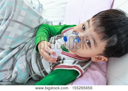 Top view of asian child holds a mask for vapor inhaler treatment of asthma on sickbed in hospital. Breathing through a steam nebulizer. Concept of inhalation therapy apparatus.