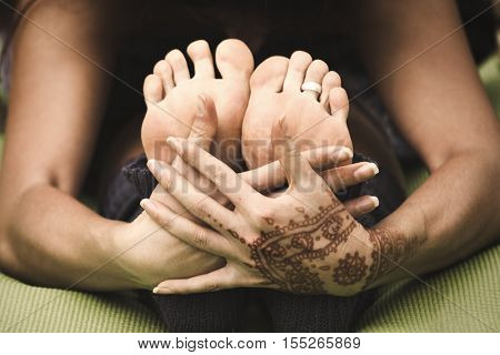 woman hands and feet closeup in yoga stretch posture, hand drawn with henna
