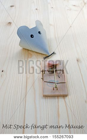 Mouse made of paper and mousetrap with bacon on wood and the german words for good bait catches mice