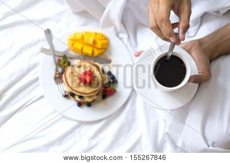 Hotcakes with fruit and coffee in bed