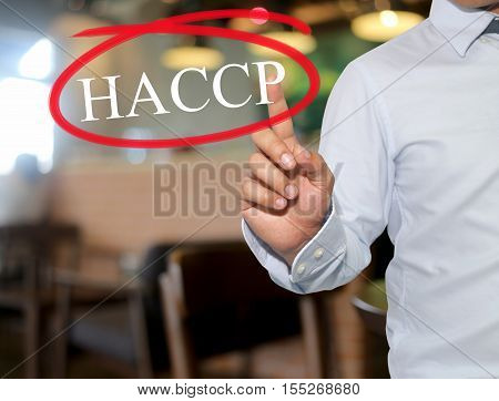 Hand of man touching text HACCP with white color on blur interior backgroundconcept of adoption to promote your business for organization.