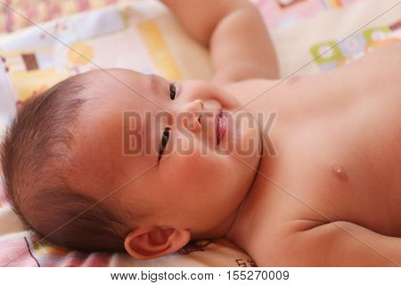 Asian baby smiling happily on bedconcept of health and growth.