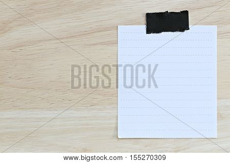 White paper blank or note paper on the brown wooden floor and You can input the message text in copy space.