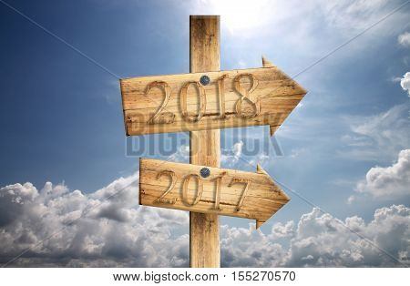 Wood sign of 2017 and 2018 in in right on blue sky backgroundconcept of a start to new year.
