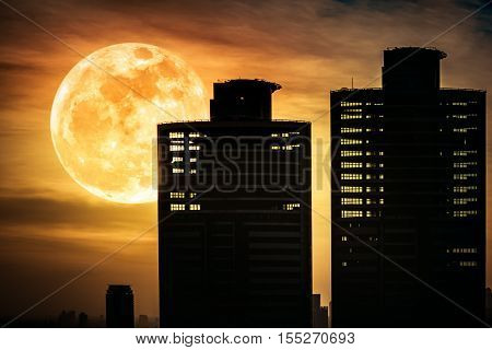 Silhouettes Of Two Skyscrapers Different  Construction With Background Of A Large Moon At Nighttime.