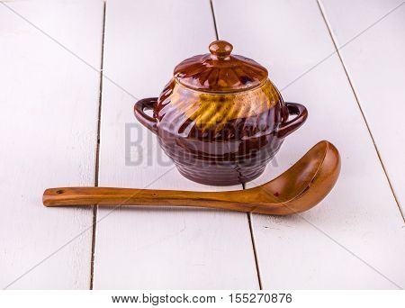 old crock pot cooking and wooden sppon on white wooden background