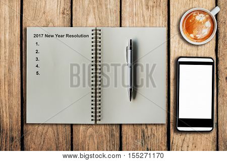 New Year Resolution 2017 as memo on notebook and coffee cup with mobile phone on table