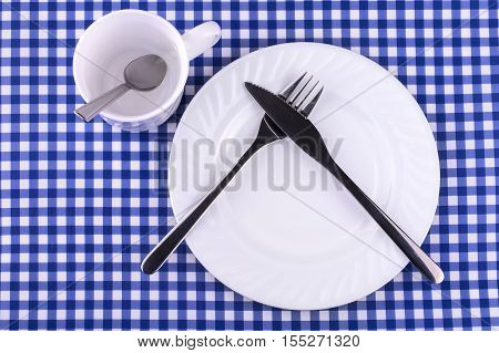 Empy Mug with spoon plate with a knife and fork on the tablecloth in a cage. View from above with copy space