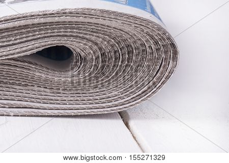 Heap of folded old newspapers on white table