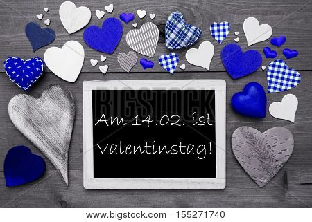 Chalkboard With German Text Valentinstag Means Valentines Day. Many Blue Textile Hearts. Grey Wooden Background With Vintage, Rustic Or Retro Style. Black And White Style With Colored Hot Spots