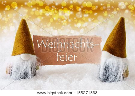 German Text Weihnachtsfeier Means Christmas Party. Christmas Greeting Card With Two Golden Gnomes. Sparkling Bokeh And Noble Background With Snow.