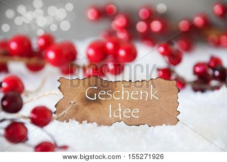Burnt Label With German Text Geschenk Idee Means Gift Idea. Red Christmas Decoration On Snow. Cement Wall As Background With Bokeh Effect. Card For Seasons Greetings