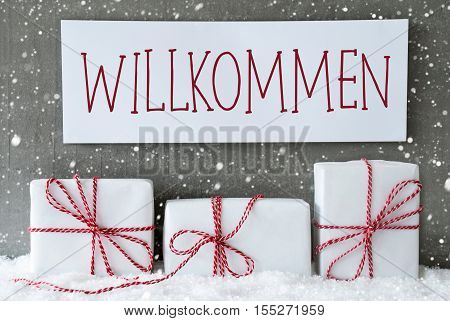 Label With German Text Willkommen Means Welcome. Three Christmas Gifts Or Presents On Snow. Cement Wall As Background With Snowflakes. Modern And Urban Style.
