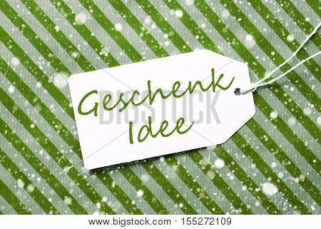 German Text Geschenk Idee Means Gift Idea. One Label On A Green Striped Wrapping Paper. Textured Background With Snowflakes. Tag With Ribbon.