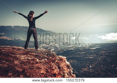 Cheering young woman standing at sunrise seaside mountain peak. Arms outstretched, freedom and happiness, achievement in mountains. Back view