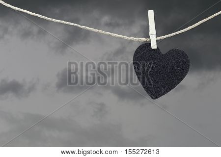 Black Heart paper hanging on a brown hemp rope on rain clouds backgroundConcepts about unrequited love and heartbreak.