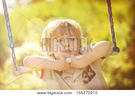Young boy hanging on a bar on a swingset