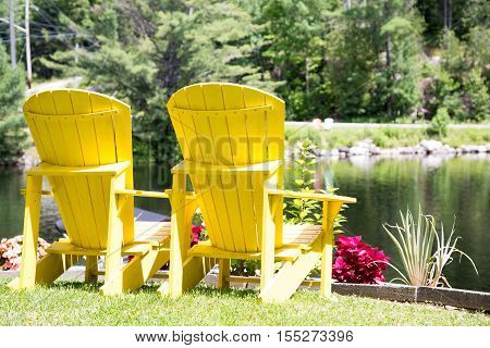 a pair of Yellow Muskoka chairs with a view of the lake at the park in Baysville Ontario