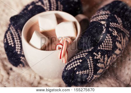hands in cozy mittens holding hot chocolate in the cup with marshmallows and candy canes in snowy weather christmas and winter time concept