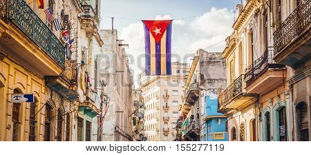 A Cuban flag with holes waves over a street in Havana, the capital city of Cuba