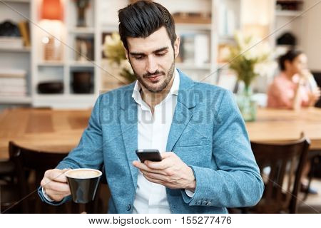 Young businessman using mobilephone, drinking coffee at cafeteria.