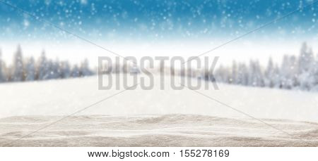 Pile of snow with blur winter panorama. Landscape with spruce trees, blue sky with sun light on background