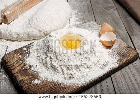 Egg yolk in the flour on wooden table in bakery.