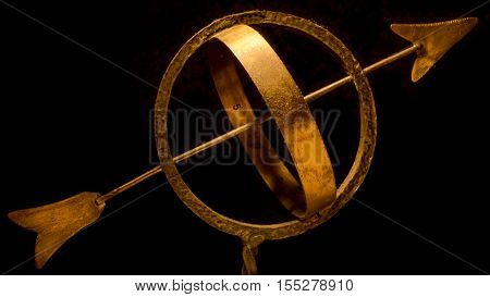 A brass sundial infront of a black background