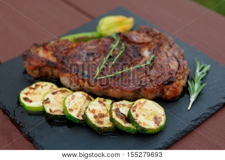 Rib-eye steak with vegetables on a slate plate