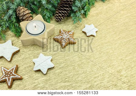 Christmas Star Shaped Cookies With Candle And Fir-tree Branches On Golden Background
