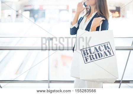 Black Friday. Shopping woman talking smartphone. Horizontal indoors shot