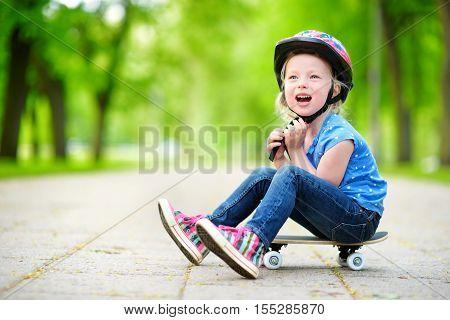 Cute Little Preteen Girl Wearing Helmet Sitting On A Skateboard