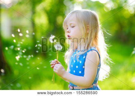 Pretty Little Blonde Girl Blowing Off A Dandelion