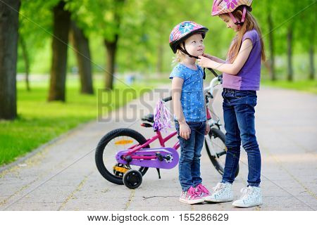 Adorable Girl Helping Her Sister To Put A Bicycle Helmet On