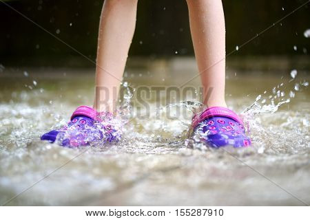 Child wearing rubber shoes jumping into a puddle on warm summer day
