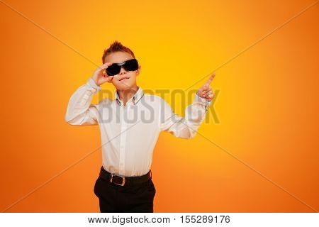 Boy in white shirt and black trousers posing in sunglasses pointing with finder up on orange background.