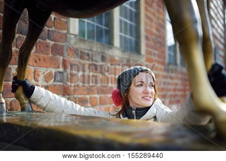 BREMEN GERMANY - MARCH 23 2016: Young tourist touching famous statue in the center of Bremen known as Bremen Town Musicians which supposed to bring good luck