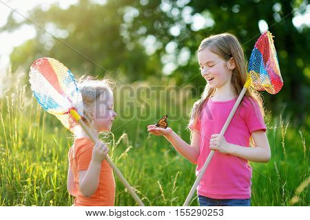 Two Little Sisters Catching Butterflies And Bugs With Their Scoop-nets